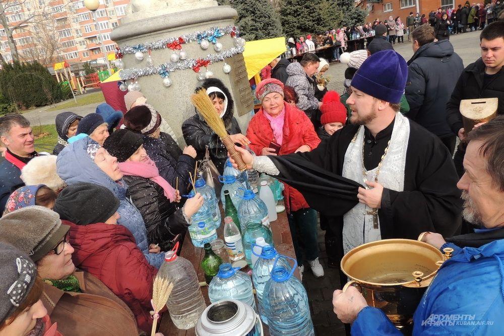 Батюшка освящает воду на территории храма Рождества Христова.