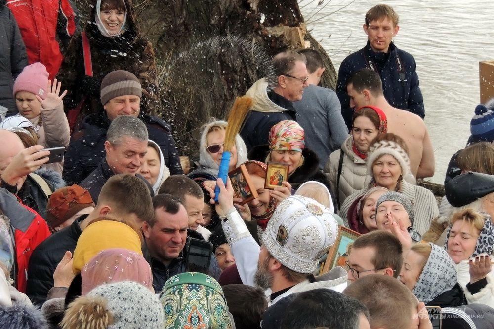 Александр Игнатов окропляет верующих святой водой.