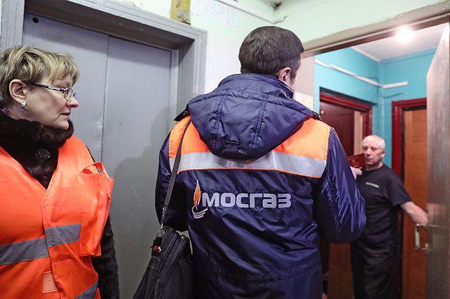 Сотрудник газовой службы показывает служебное удостоверение жильцу квартиры.