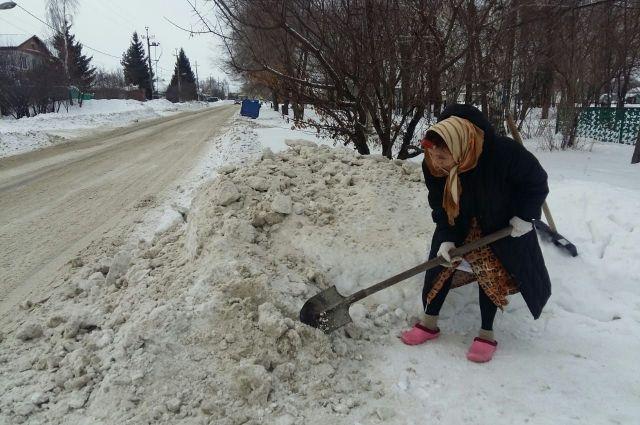 Местная «Агафья Лыкова» расчищает подход от дороги к своему дому двумя лопатами.