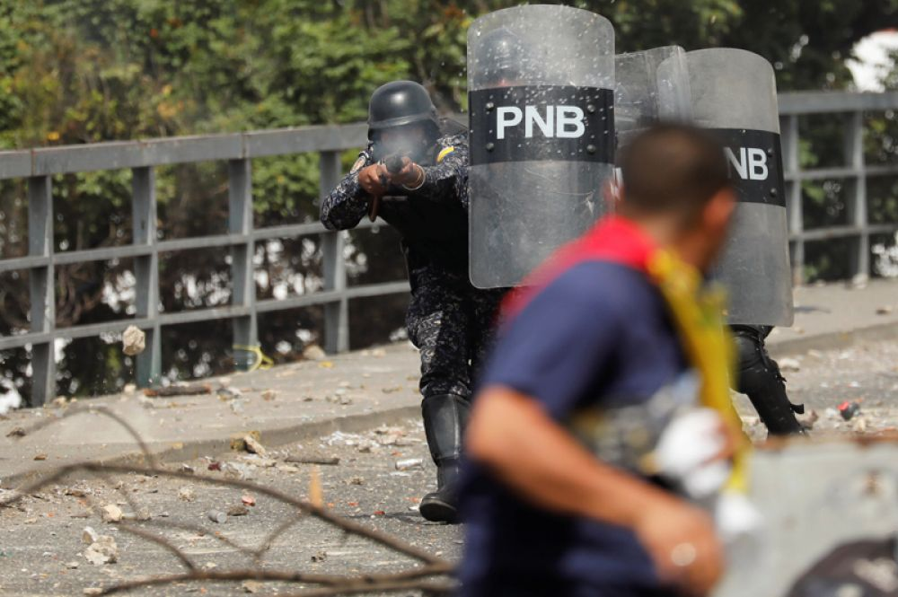 Полицейский стреляет резиновыми пулями в демонстранта.