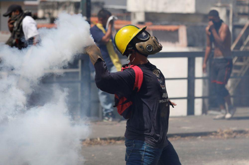 Демонстрант бросает гранату со слезоточивым газом во время акции протеста против правительства Николаса Мадуро.