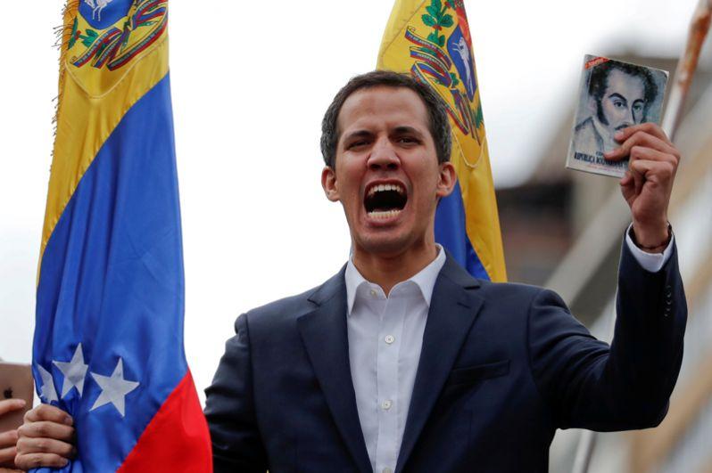 Хуан Гуайдо держит копию конституции Венесуэлы во время митинга против президента Венесуэлы Николаса Мадуро в 61-ю годовщину свержения бывшего диктатора Маркоса Переса Хименеса в Каракасе.