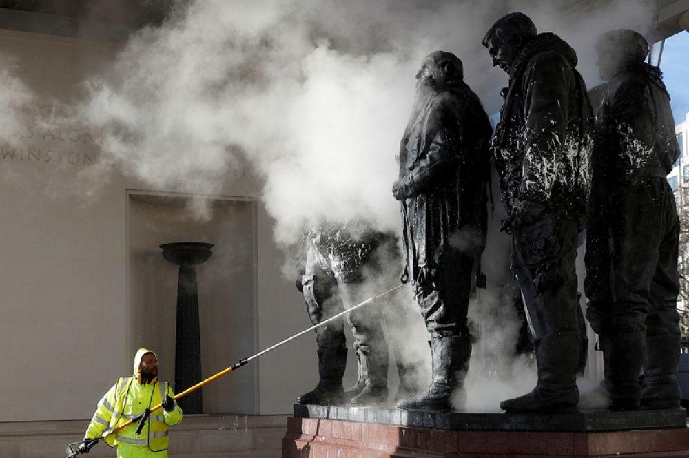 Рабочий чистит испорченный краской мемориал бомбардировщикам ВВС Великобритании в Грин-Парке Лондона.