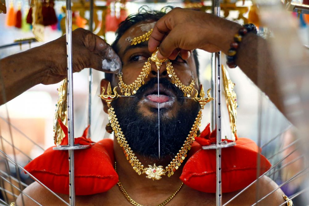 Мужчина прокалывает язык во время индуистского праздника Тайпусам в Сингапуре.