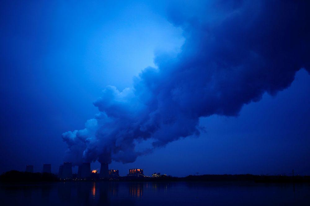 Пар поднимается из градирен электростанции в Йеншвальде, Германия.