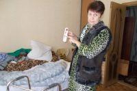 Людмила Чернышёва в «боевой экипировке» показывает градусник, который совсем не радует показаниями.