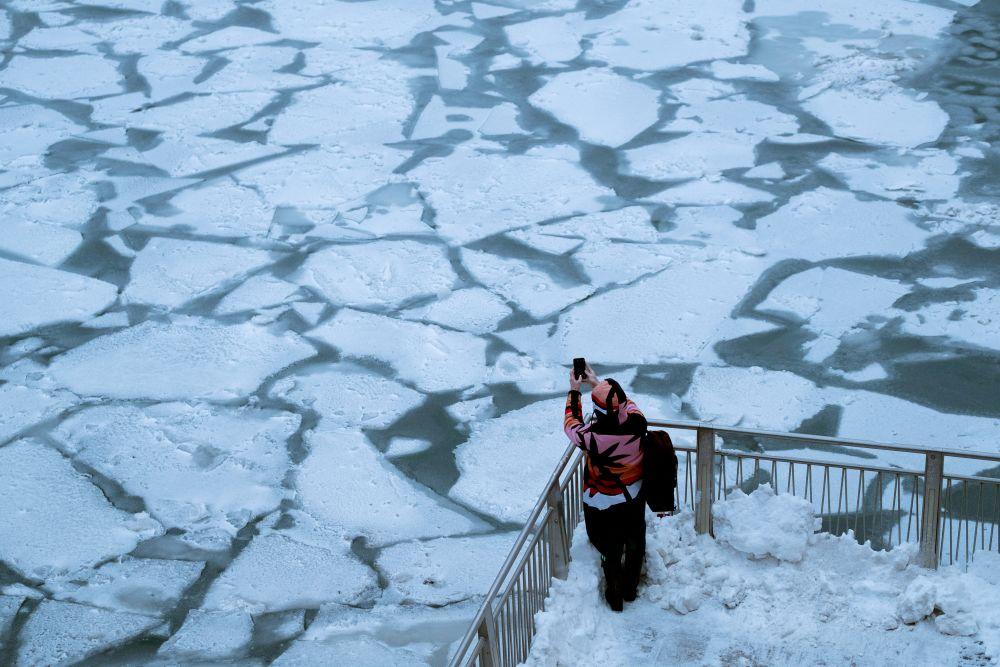Пешеход фотографирует лед на реке Чикаго.