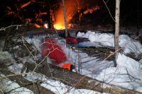 Трое туристов ночевали в снежном убежище, двое грелись у костра.