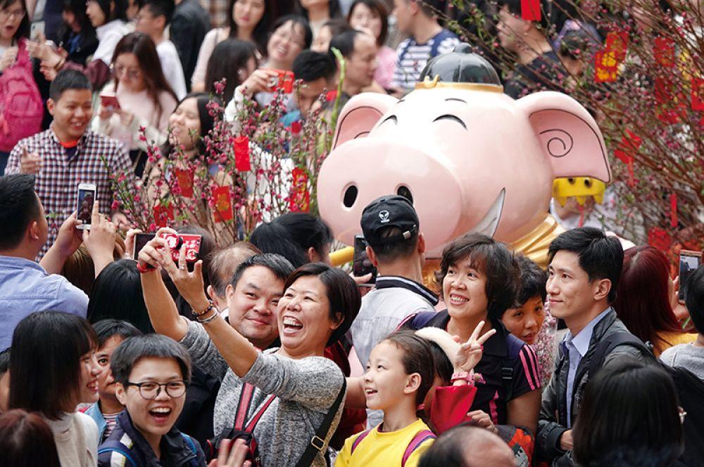Посетители фотографируются с инсталляцией свиньи на цветочной ярмарке в преддверии нового года в Гуанчжоу, Китай.