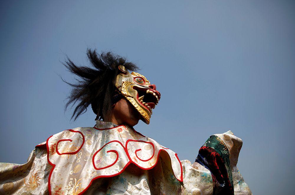 Танцор в маске и традиционной одежде выступает во время празднования нового года в Катманду, Непал.