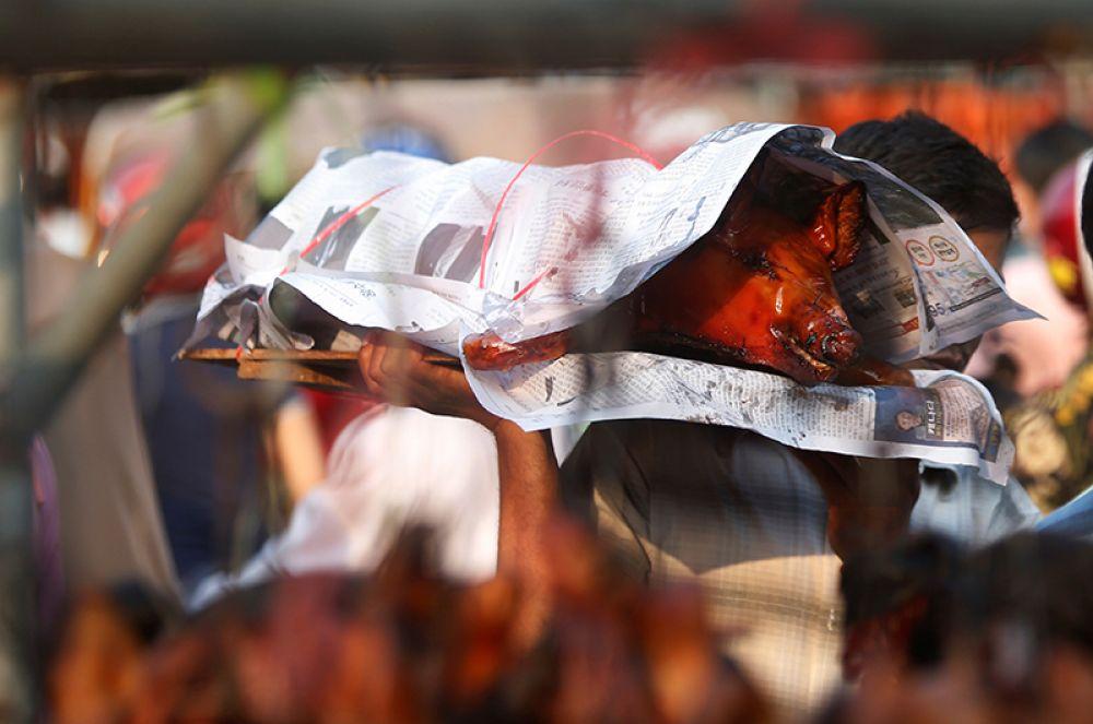 Мужчина покупает жареных свиней на улице во время празднования нового года в Пномпене, Камбоджа.