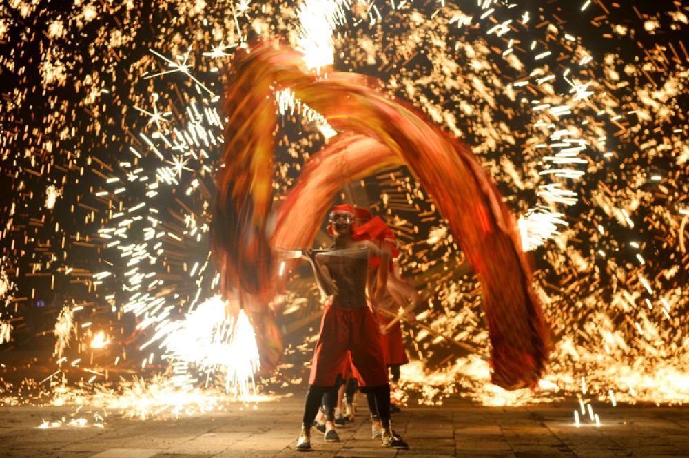 Артисты исполняют танец огненных драконов в первый день нового года по восточному календарю в Цзаочжуане, Китай.