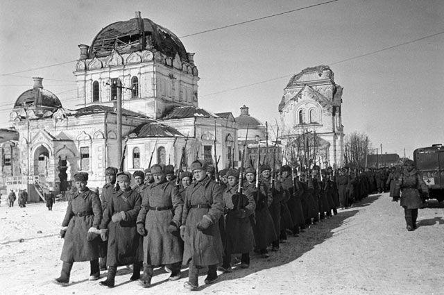 В ходе Ржевско-Вяземской операции войсками Западного фронта был освобожден Гжатск (Гагарин). Колонна советских войск проходит по улице освобожденного города.