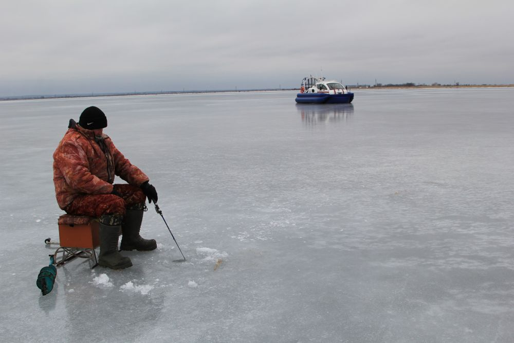 Инспекторы выходят с судна и идут общаться с рыбаками, раздают им памятки о мерах предосторожности на воде.