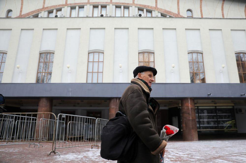Мужчина с цветами перед началом церемонии прощания с актером Сергеем Юрским у здания театра имени Моссовета.