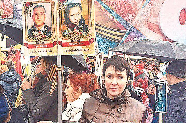 Анна Тув с фотографиями мужа и дочери, погибших от обстрела Горловки, на акции «Бессмертный полк» в Москве, 2017 г.