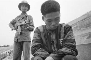 Вьетнамский солдат держит под прицелом военнопленного китайской армии.