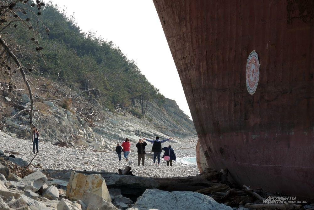 Туристы фотографируются на фоне судна.