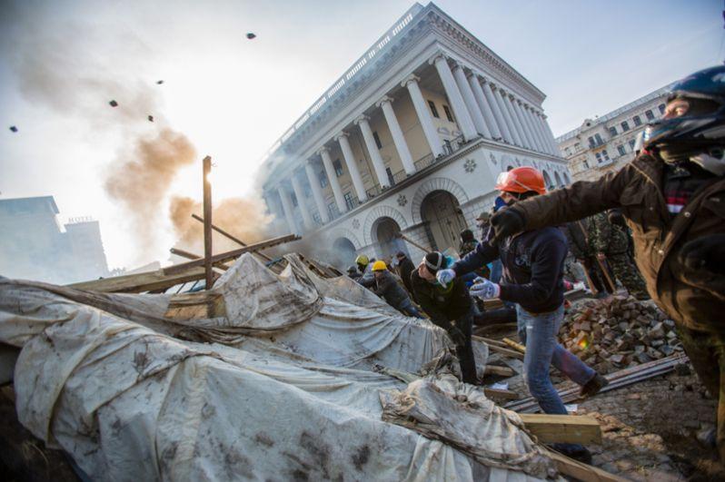 Сторонники оппозиции кидают камни на площади Независимости в Киеве.