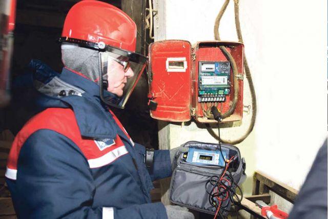 Энергетики с помощью специального оборудования проверяют прибор учёта.