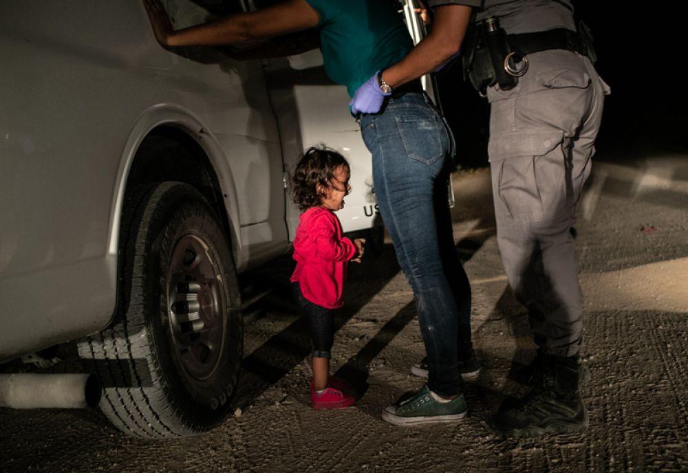 Яна из Гондураса плачет, пока ее мать Сандру Санчес обыскивает агент пограничной службы США, Макаллен, штат Техас.