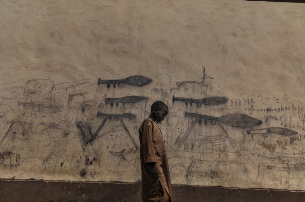Мальчик-сирота проходит мимо стены с рисунками гранатометов в Боле, Чад.