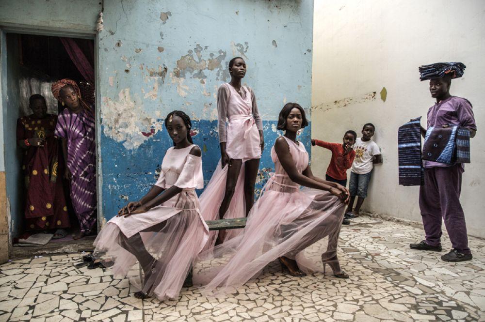 Девушки демонстрируют дизайнерские наряды в окружении любопытных жителей в столице Сенегала Дакар.