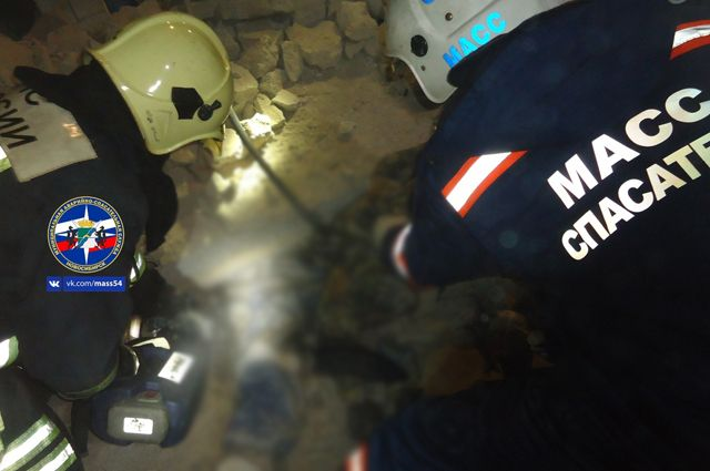 Спасатели подняли две бетонные плиты, чтобы вызволить тело.