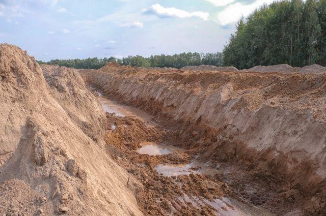 В траншее, которую роют вдоль строящейся дороги, уже поднимается вода.