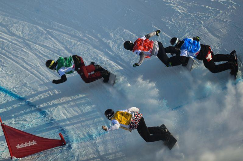 Спортсмены в полуфинале на трассе мужского сноуборд-кросса соревнований по сноуборду на XXIX Всемирной зимней Универсиаде 2019.