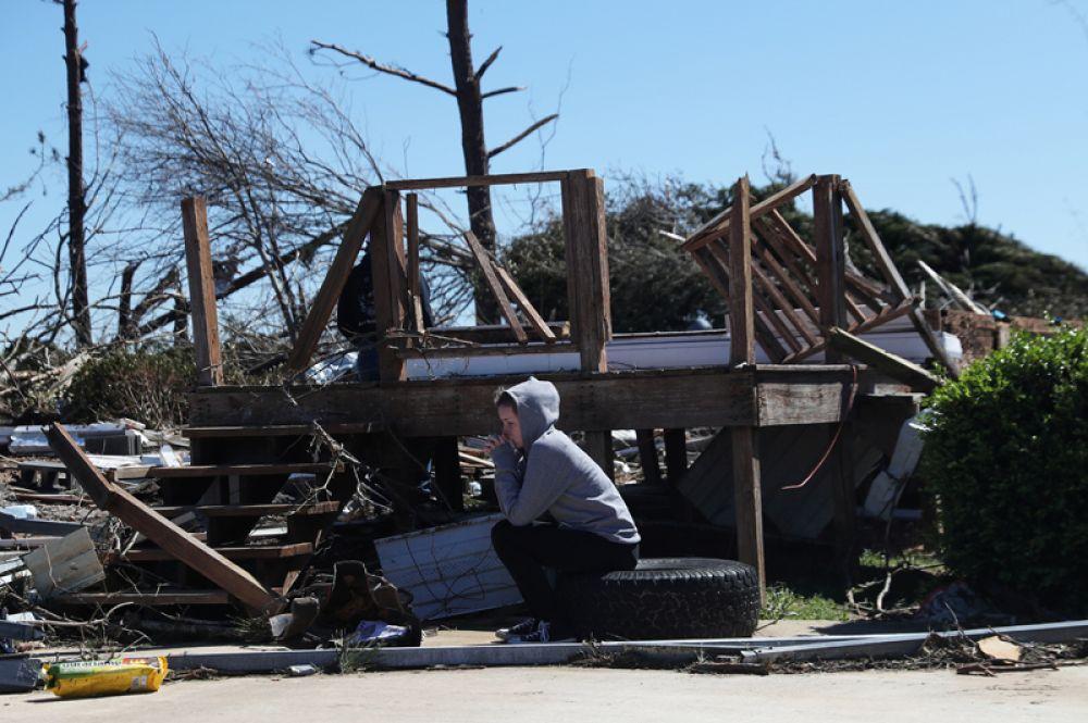 Девушка возле разрушенного дома.