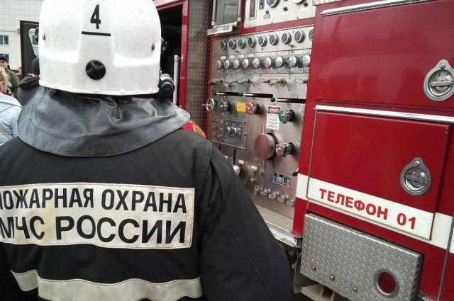 Пожарные вывели из горящего дома женщину.