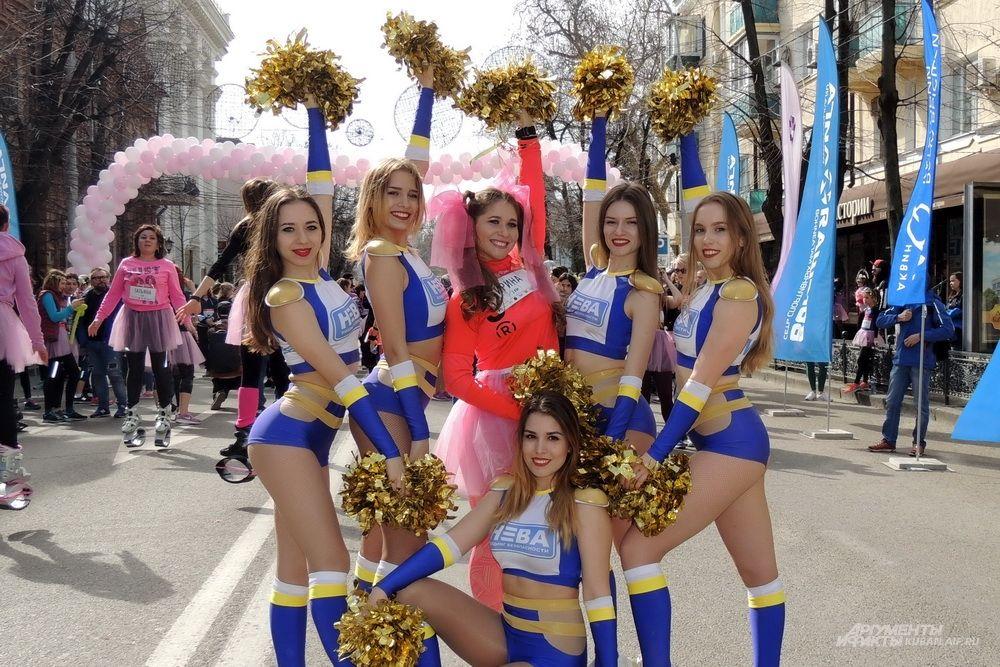 Участница забега фотографируется с девушками из группы поддержки.
