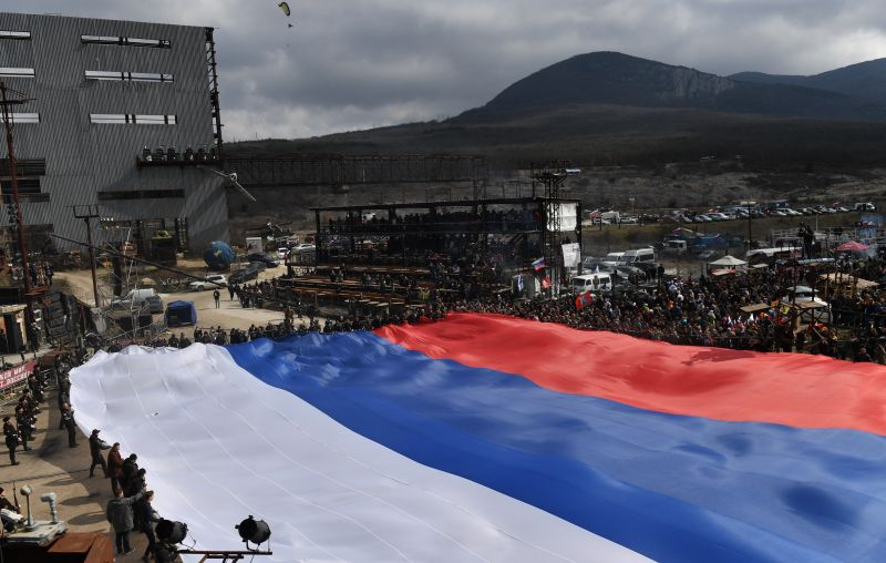 Участники автопробега в честь пятилетия всекрымского референдума и воссоединения полуострова с Россией растягивают гигантский флаг России на горе Гасфорта в Севастополе.