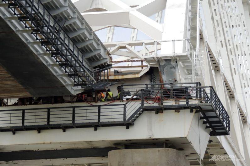 Строители выполняют работы у основания железнодорожной арки моста.
