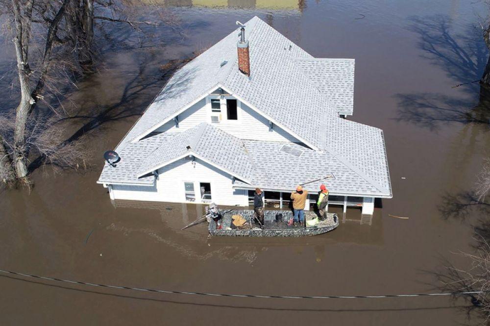 Спасатели пытаются достать кошек из затопленного дома возле Гленвуда, Айова.