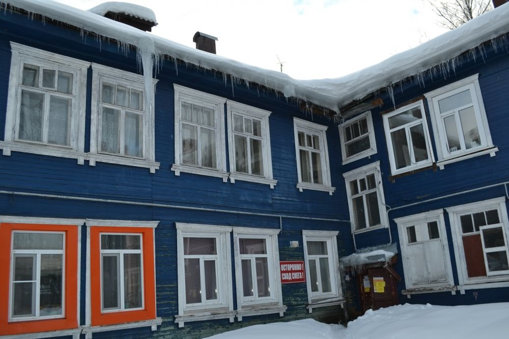 """Аналогичную картину можно наблюдать и на двух соседних домах: №2 и №4. С покатой крыши свисают сосульки. Видимо, они здесь частые гости, поэтому объявления """"Осторожно! Сход снега!""""прикручены к стенам дома основательно, их не снимают даже летом."""