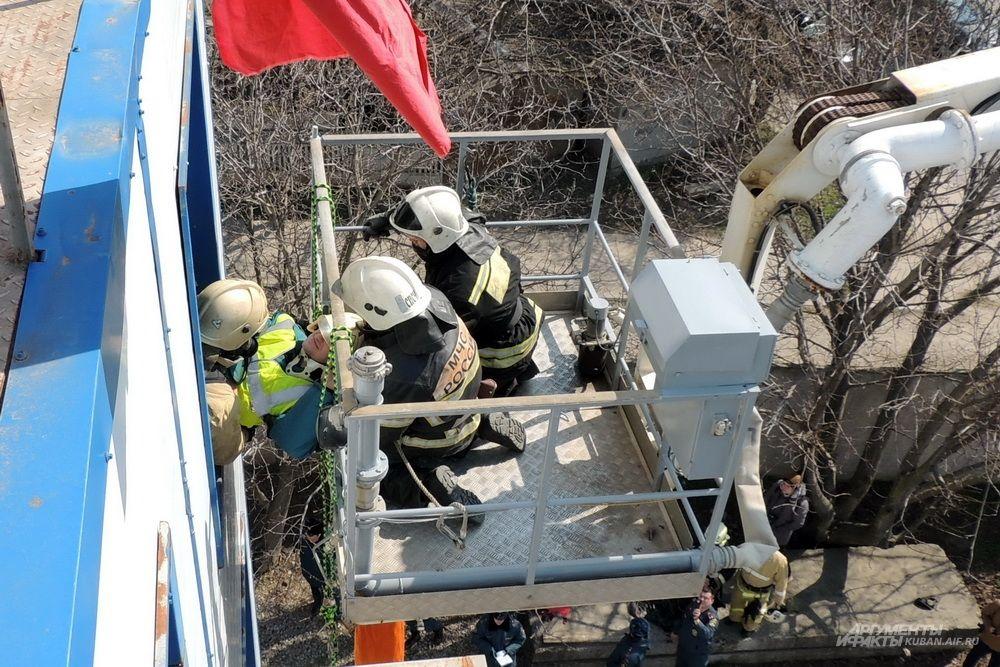 А здесь пожарные передают коллегам в люльку автоподъёмника живого «пострадавшего».