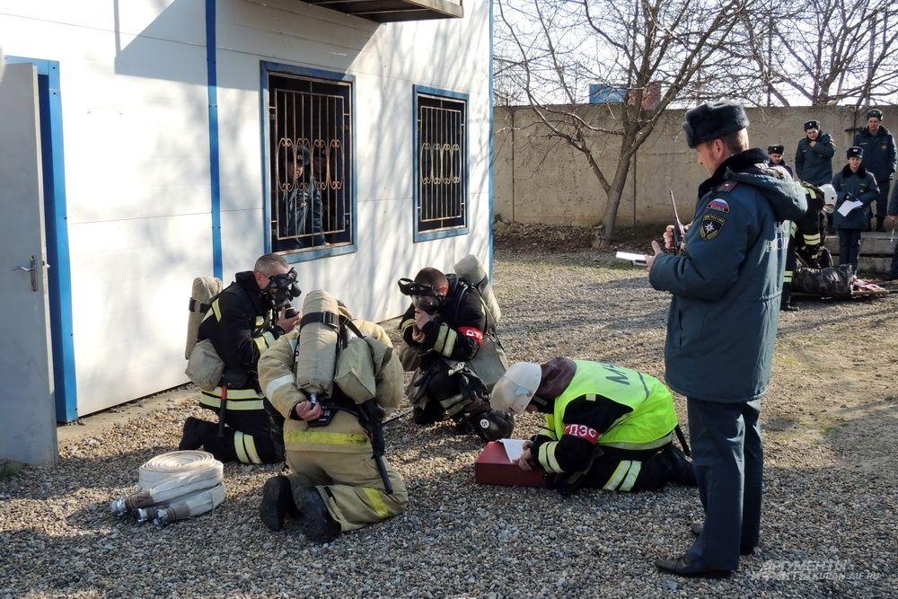 Огнеборцы готовятся к тушению условного пожара под пристальным взором члена жюри.