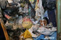 Если посмотреть в окно квартиры снаружи дома, видно, что в помещении всё до потолка заставлено мусором.