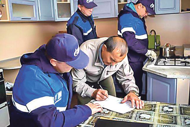 Специалисты газовой службы одеты в спецодежду сине-голубого цвета с изображением логотипа компании.