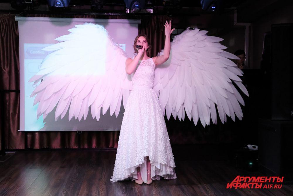 Карина Пирожкова из школы № 145 появилась на сцене в белом платье с крыльями из перьев и спела популярную песню: «Помолимся за родителей».