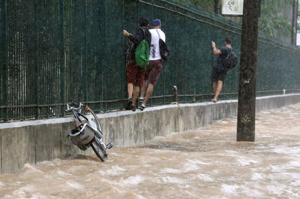 Местные жители на затопленной улице в районе Жардин-Ботанику в Рио-де-Жанейро.