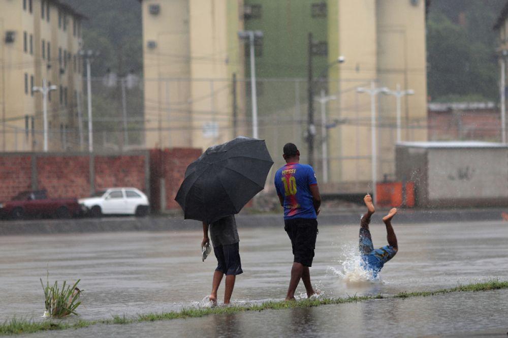 Мужчина ныряет в затопленный канал в районе Фазенда Ботафого в Рио-де-Жанейро.