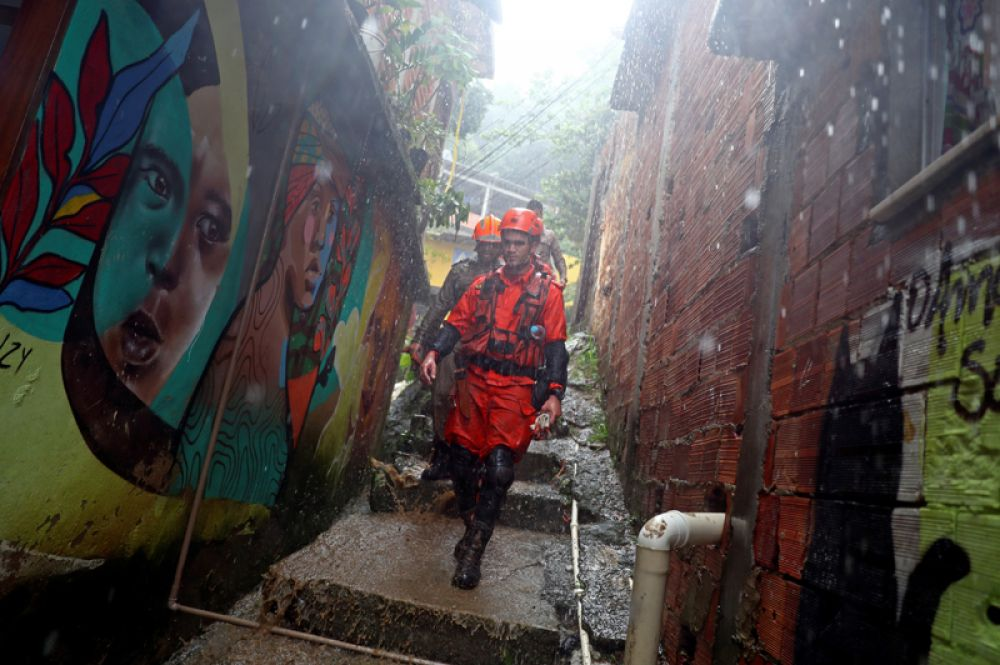 Спасатели бегут к месту схождения оползня в трущобах Рио-де-Жанейро.