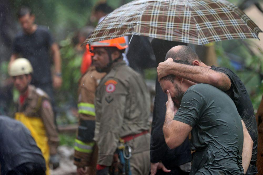Местные жители на месте оползня после проливных дождей в Рио-де-Жанейро.