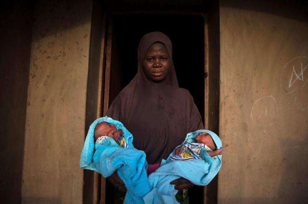 Мать держит на руках новорожденных близнецов, появившихся на свет четыре дня назад.