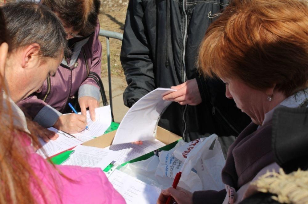 Люди активно подходили к столу с петициями и расписывались.