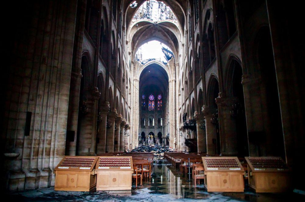 Сгоревшая крыша и поврежденные витражи внутри собора.